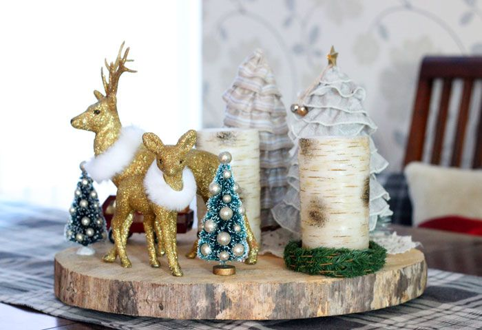 Designer Virginia Fynes placed an array of Christmas decor on top of wood slice to create a focal point on her dining room table.   See more at Fynes Designs.