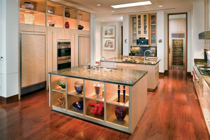 """This kitchen features display niches above the cabinetry and inside the base of one of two islands. """"It seemed appropriate to incorporate display shelves here for the wife's collection of glass, pottery and artifacts from around the world,"""" Petruccelli says. Watercolors by Bobbie Hanson Riddle grace the far wall."""