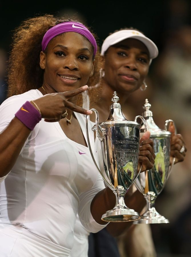 """LONDON, ENGLAND - JULY 07: Serena Williams (L) and Venus Williams of the USA celebrate with their winners trophies after their Ladiesâ¬"""" Doubles final match against Andrea Hlavackova and Lucie Hradecka of the Czech Republic on day twelve of the Wimbledon Lawn Tennis Championships at the All England Lawn Tennis and Croquet Club on July 7, 2012 in London, England. (Photo by Julian Finney/Getty Images)"""