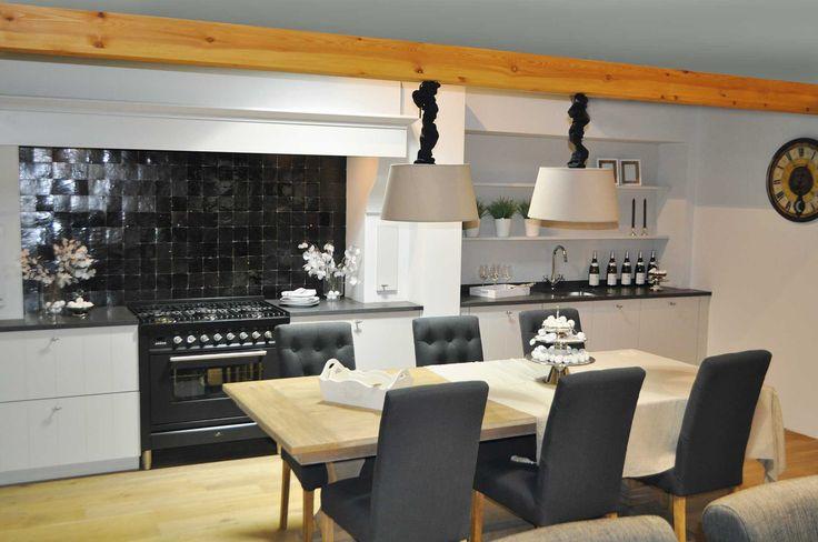 Landelijke, witte keuken met zwarte tegels. Deze landelijke keuken heeft twee hoofdkleuren die in meerdere elementen terugkomen. De keukenkasten en muren zijn wit en zorgen voor een lichte ruimte. Dit staat in contrast met het zwarte Boretti fornuis en mozaïektegels aan de wand. De grijze kleur van het werkblad komt dan weer terug in de stoelen. De houten balk aan het plafond zorgt voor een warm en landelijk accent.