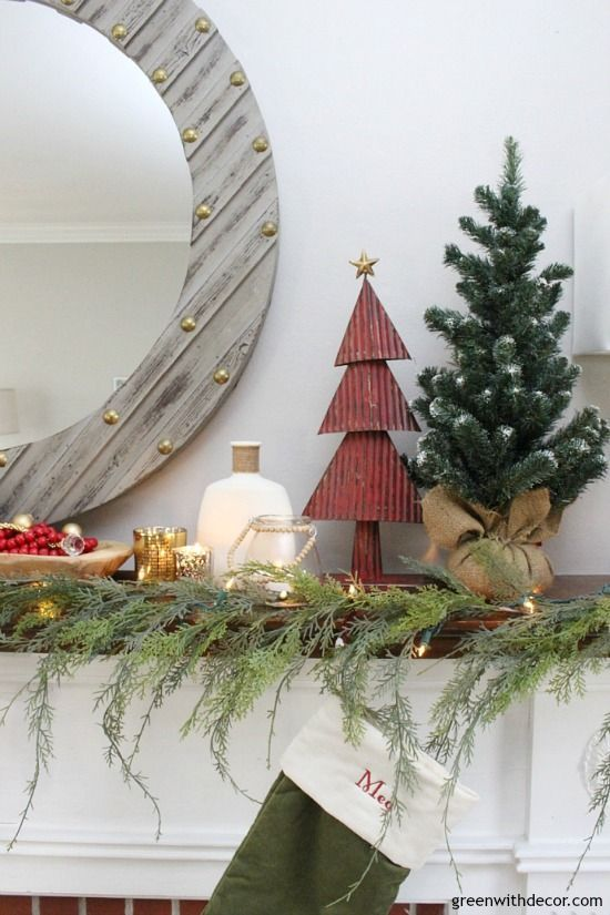A traditional Christmas mantel - full of red, green, metallic and neutral pieces. Love the faux garland with the mini Christmas trees!