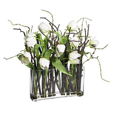 White tulips with twigs in glass vase