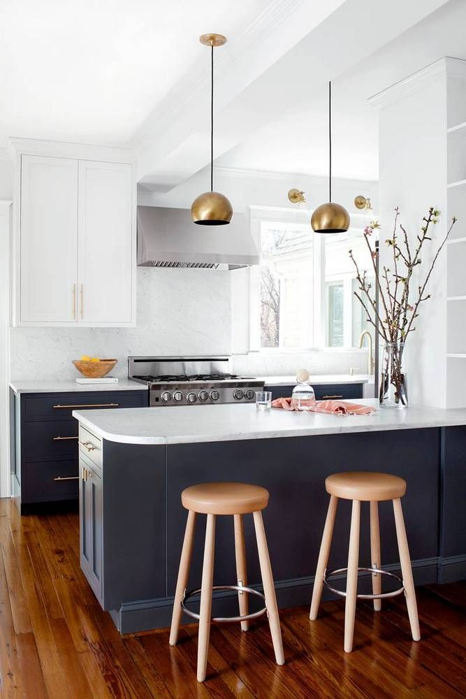 Minimalist kitchen with gray cabinents and brass pendant lamps