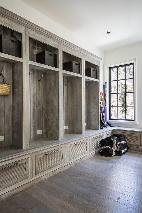 Rustic country mudroom features a wall of built-in lockers with open and closed storage as well as a built in storage bench.