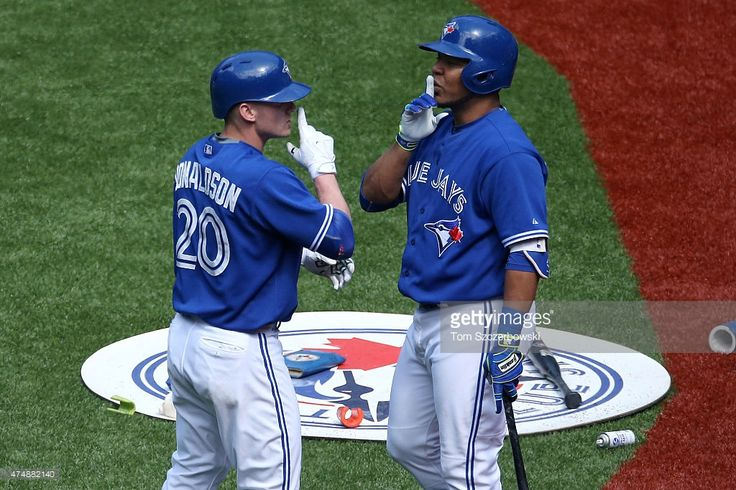 Josh Donaldson #20 of the Toronto Blue Jays is congratulated by Edwin Encarnacion #10 after hitting a game-tying solo home run in the tenth inning during MLB game action against the Chicago White Sox on May 27, 2015 at Rogers Centre in Toronto, Ontario, Canada.