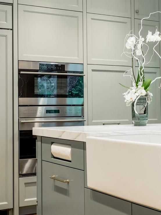 A gorgeous gray kitchen island topped with a marble countertop is fitted with flat front gray cabinets fitted with a farmhouse sink and a built in paper towel holder while beside the island stacked gray cabinets frame a stainless steel oven mounted beneath a stainless steel microwave.