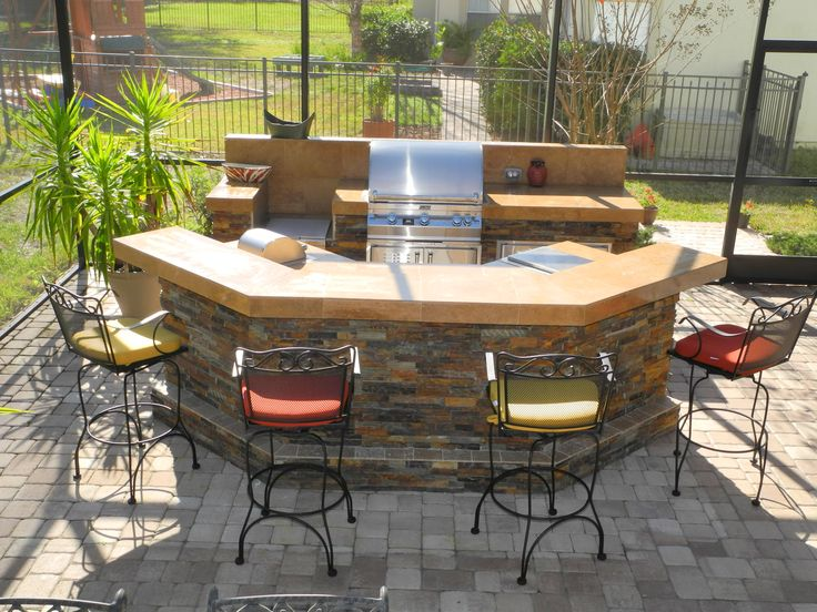 Outdoor kitchen with stacked stone and travertine countertop.  Separate bar island with seating for 4-6. Designed and constructed by Creative Design Space, Fleming Island FL.