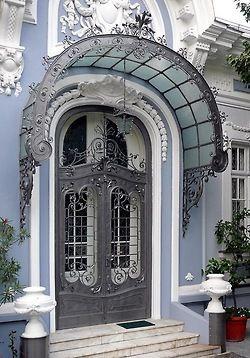 Linda porta de madeira com detalhes em vidro e ferro forjado, e um toldo adornado, fazendo um maravilhoso conjunto.
