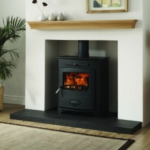 Black wood or pellet stove with mantle. Black hearthstone, white walls, and light wood mantle and floors.