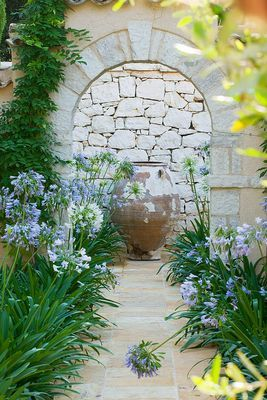 CORFU, GREECE: DESIGNER: DOMINIC SKINNER - MEDITTERANEAN STYLE GARDEN - VIEW ALONG PATH THROUGH STONE ARCH TO FOCAL POINT TERRACOTTA CONTAINER AND AGAPANTHUS