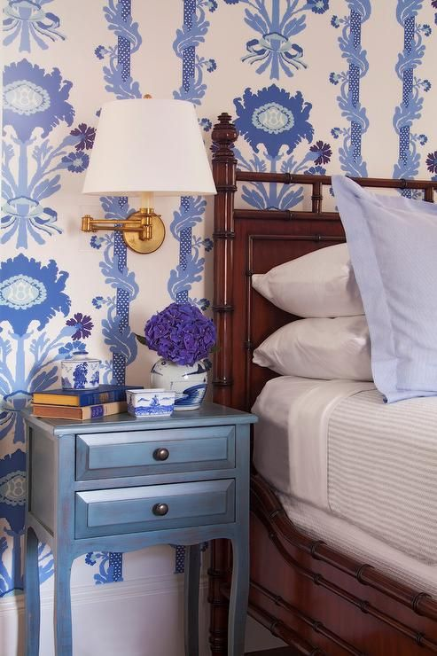A brown bamboo bed sits in front of a wall clad in white and blue wallpaper and beside a blue nightstand adorned with oil rubbed bronze hardware lit by a brass swing arm sconce.