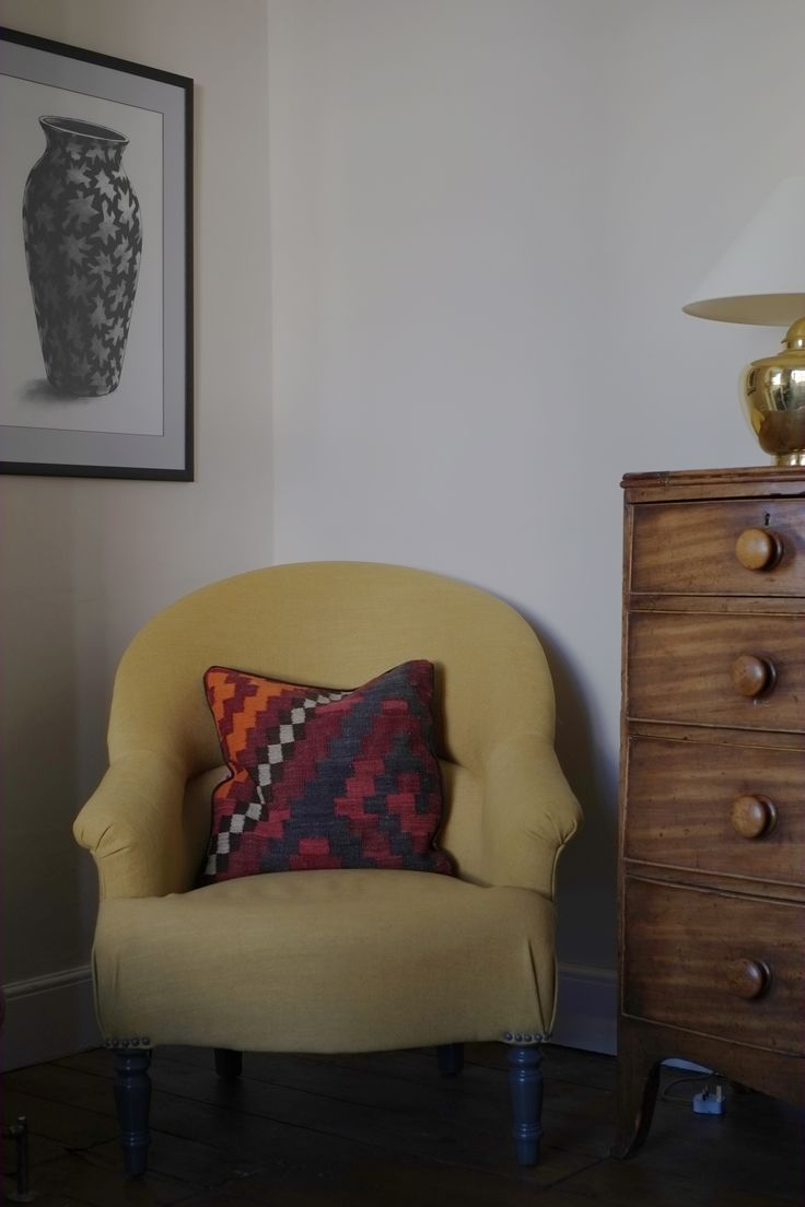 Made.com armchair with bow-front chest of drawers and charcoal art.