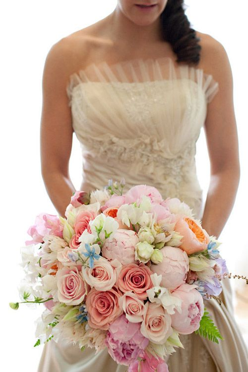 Pastel bouquet consisting of Peonies, Tweedia and Roses in shades of pink. Gorgeous wedding dress too!