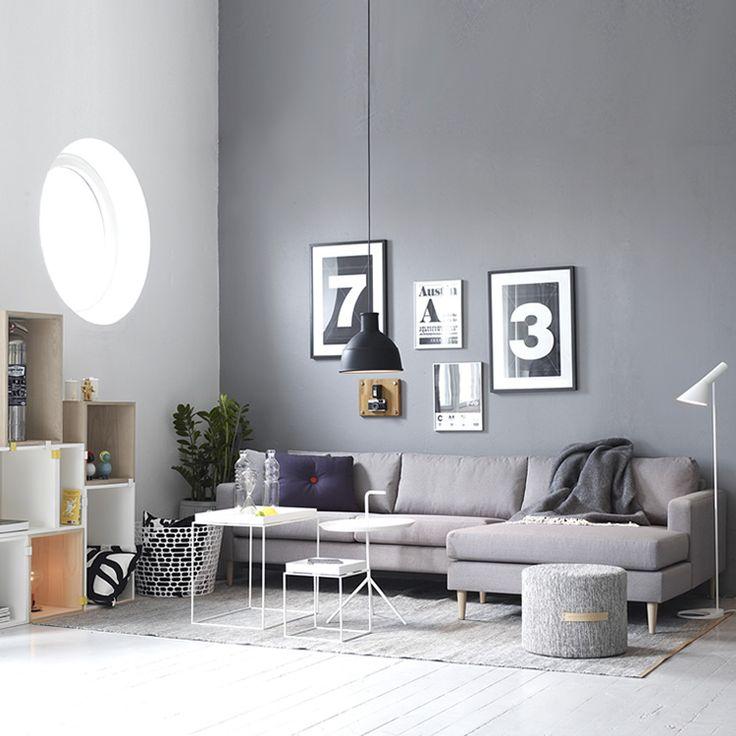 Salon avec une fenêtre ronde dans un décor gris / Living room with a round window in grey decor
