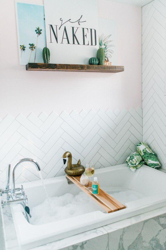 Pink and marble bathroom design. Herringbone tile. Tropical leaf towel. Get Nake sign. Swan floatie. Cactuses.