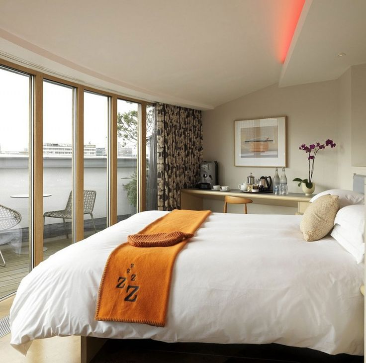 Love the colors on this bright orange blanket on a white bed the zetter hotel