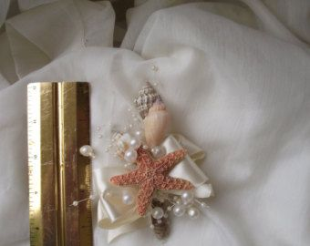 Perfect for a beach / destination wedding or event, I have combined a white knobby starfish with a conch shell, a few little pearls, and jute roping to create an awesome boutonniere for your nautical themed wedding or event that will match any attire. Its not very heavy and includes two pins to attach to your Grooms or Groomsmens jacket or shirt. Smaller and larger sizes available, as well as matching corsages and wedding bouquets! Similar boutonnieres here…