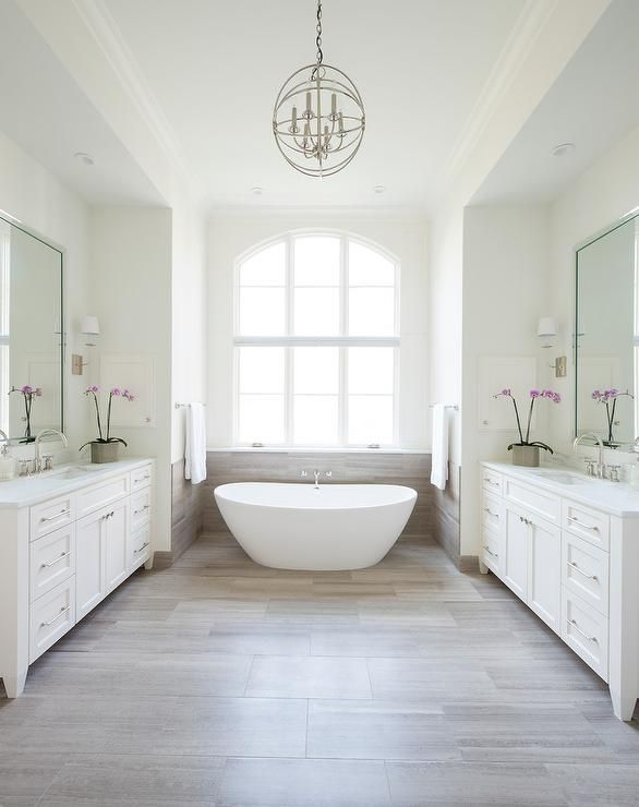 Restful white bathroom is equipped with facing white washstands fitted with Kohler faucets fixed under beveled vanity mirrors lit by nickel sconces and a nickel sphere pendant hung over Daltile Chenille White Tiles leading to a bathtub nook boasting MTI Elise Tub sat under an arched window.