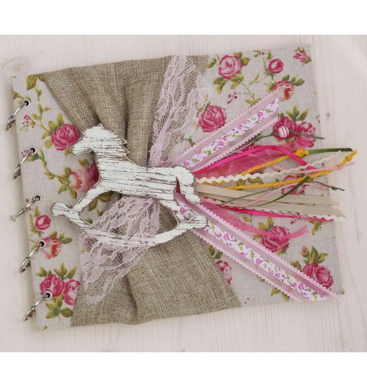 Χειροποίητο Βιβλίο Ευχών Βάπτισης αλογάκι καρουζέλ. Βιβλίο ευχών ντυμένο με μπεζ ύφασμα με ροζ λουλούδια, διακοσμημένο με ξύλινο χειροποίητο αλογάκι καρουζέλ.  Φύλλα :35 χρώμα φύλλων : ροζ παστέλ  Υπάρχει η δυνατότητα να γράψουμε κάτω δεξιά σε κάθε σελίδα το όνομα του παιδιού σας, ή