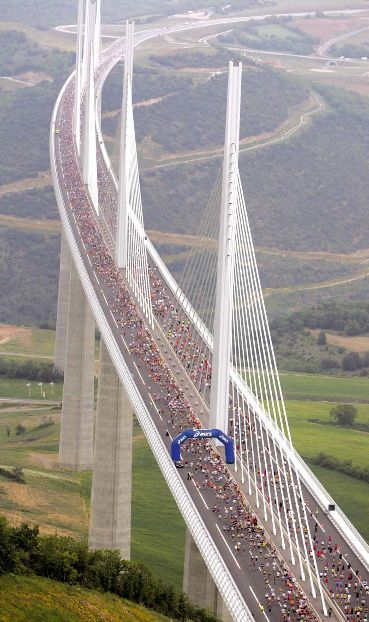 The World's Tallest Bridge, Southern France. Millau Viaduct in France. As high as 1125 feet above the Tarn Valley. Milau has a total length of 8071 feet with the longest single span of 1122 feet. Bridge deck is supported by 7 pillars and weighs 36,000 tons. 7 towers, each 292 feet tall and weighing 700 tons, fitted to supporting pillars.