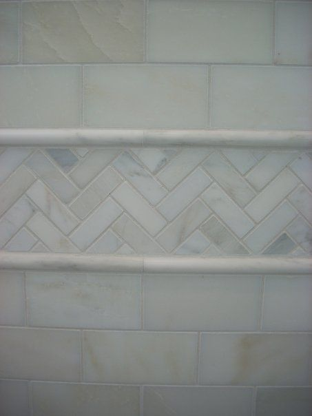 Accent herringbone with marble subway tiles.  The pencil moldings are a great frame.  When you change patterns a molding to separate them makes a statement.  If tiles aren't the same height, the molding hides that and the look is finished.
