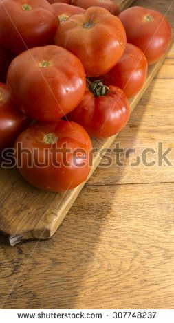 Freshly picked tomatoes on wooden chopping board and wooden table.