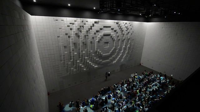 Hyper-Matrix is a kinetic landscape installation created for the Hyundai Motor Group Exhibition Pavilion in Korea, the 2012 Yeosu EXPO site. The installation consists of a specially made huge steel construction to support thousands of stepper motors that control 320x320mm cubes that project out of the internal facade of the building. The foam cubes are mounted to actuators that move them forward and back by the steppers, creating patterns across the three-sided display. Comprised of what at…