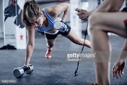 Stock Photo : Fitness trainer keeping time with woman doing dumbell push-ups