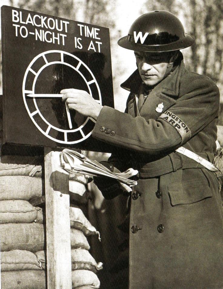 An air-raid warden sets a black-out time clock indicator at an A.R.P. post near London - 1 November 1939