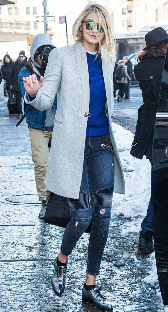 Gigi Hadid wears a blue sweater, gray coat, motorcycle jeans, mirrored sunglasses, and metallic oxfords