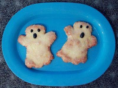 Halloween - voedsel: pizza geesten. Gemaakt van pita-brood, tomatensaus, mozarella en zwarte olijven als ogen. Hartige snack voor tijdens een Halloween-feest.