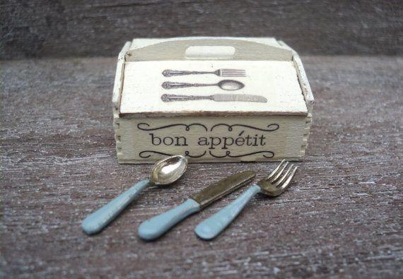 Una hermosa caja de madera de 1 pulgada o 1:12 escala para guardar tus cubiertos de casa de muñecas. La caja tiene dos tapas y está pintada en un color grisáceo. Tiene un asa de transporte. Dos lados de la caja están decorados con el texto bon appétit. La imagen de una cuchillería establece en una de las tapas. Una adición perfecta para tu cocina de casa de muñecas, sala comedor, panadería o confitería. Viene completo con un juego de cubiertos (1 cuchara, 1 tenedor, 1 cuchillo) con…