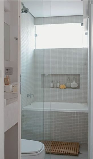 Separate shower and tub share space behind a glass wall in a small bath