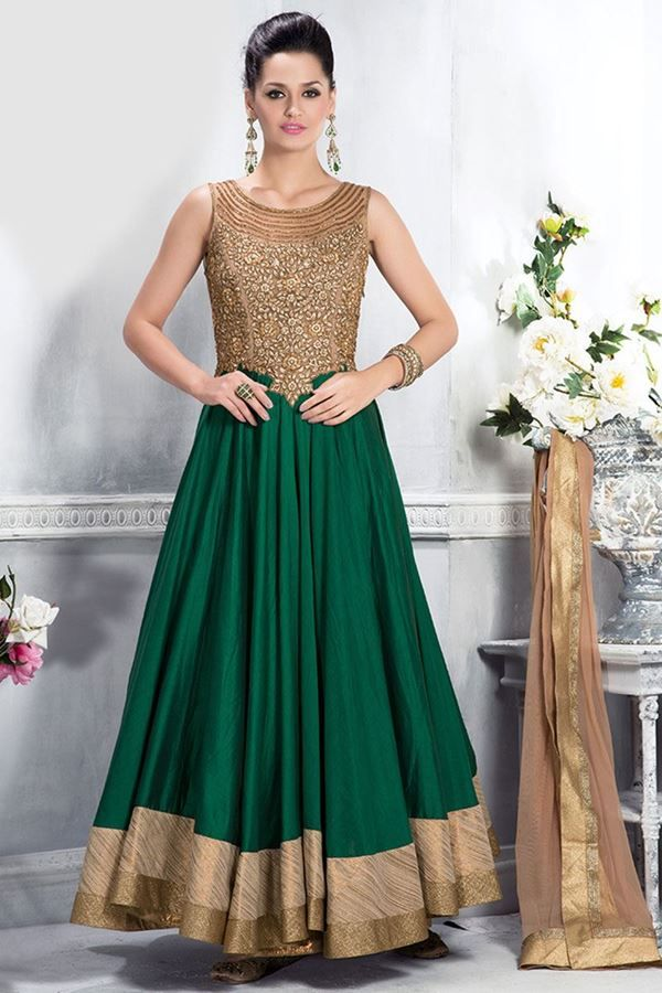 Pull together a chic look by wearing this green & beige colored suit set from the house of Aishwarya design studio. Exquisitely designed, this uneven style suit will surely set you in spotlight and bring you loads of compliments. High yoke is fully embroidered with katdana, zardosi kundan and thread work in floral pattern and kameez is edged with fancy lace borders. Back neck is of net and team matching color accessories with this suit to make you look even more elegant.