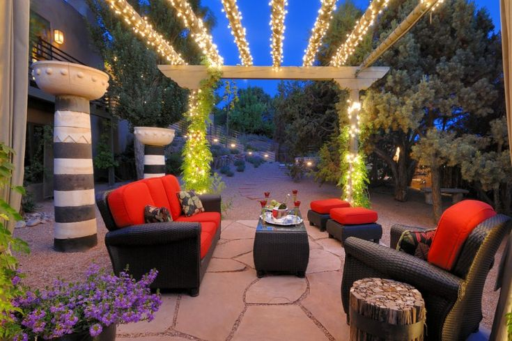patio with black rattan chairs with red cushion, matching tables and ottomans under a pergola with light strands twisted of Stunning Outdoor Lights for Gazebo and Pergola