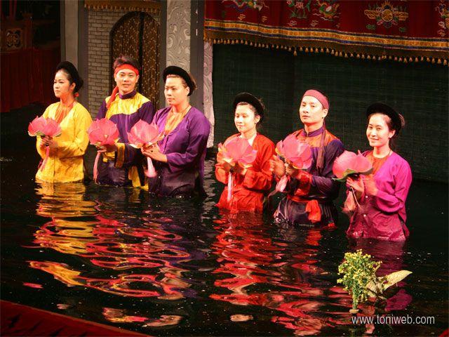 Teatro Marionetas sobre el Agua Mua Roi Muoc - Water Puppetry Theatre. En el escenario, hay un pequeño estanque lleno de agua, imitando los campos de arroz, desde donde los actores manejan las marionetas. La narrativa casi siempre esta relacionada con leyendas de dragones o seres mitológicos.