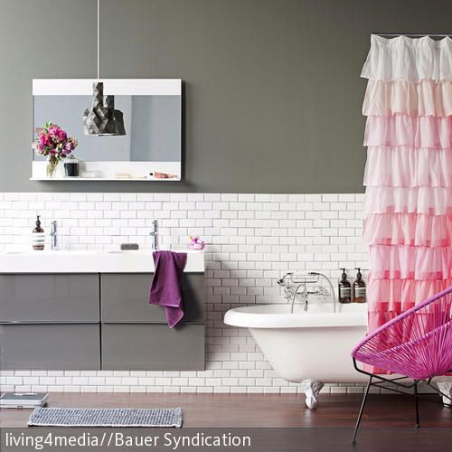 Vorhang auf für einen absoluten Hingucker! In dem sonst eher kühlen, modernen Badezimmer ist, neben dem pinken Sessel in Flecht-Optik, das Highlight der…