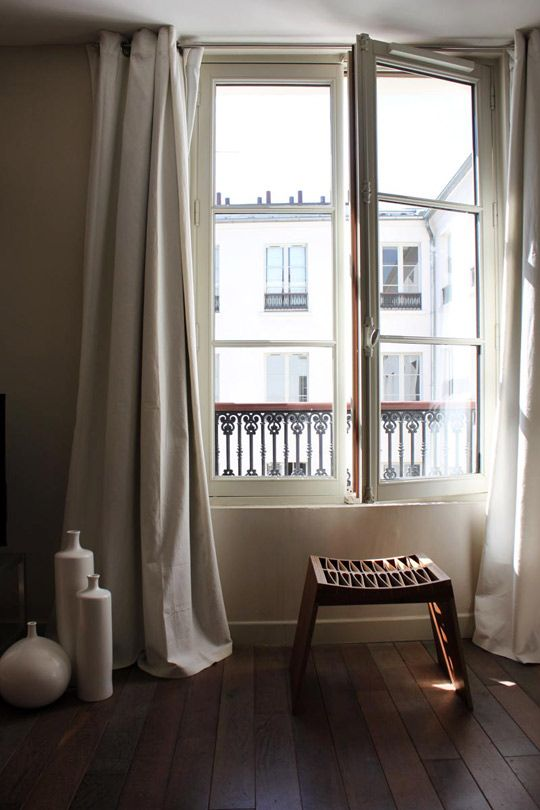 I ADORE hanging curtains at the top of the wall. Elongates the line and makes the room feel more grand and tall. This is such a beautiful example from an Parisan apartment.