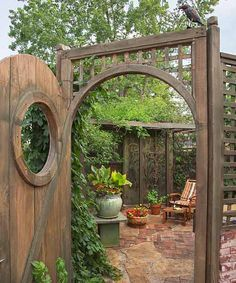A porthole fashioned from #salvagewood gives a glimpse into this secluded #beergarden with a vine of hops! #gardenescape | Photo: Dale Horchner
