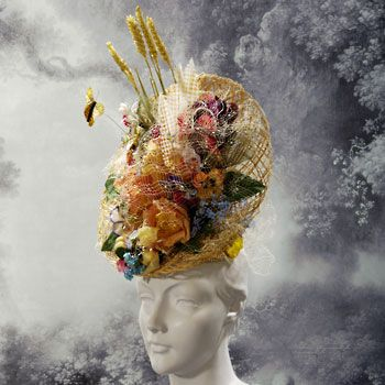 Stephen Jones- Royal Horticultural Society floral hat this busy design is filled with different flower shapes and colours to fill the inside of this upside down dome netted base.