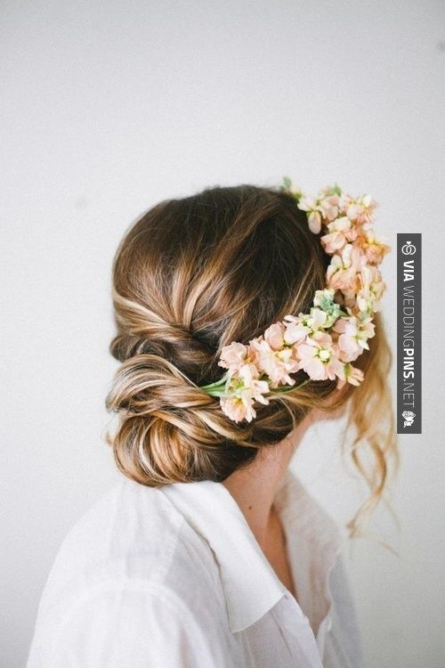 Low chignon wedding hairstyle with ombre hair color from brunette to blonde and accented with a pink floral crown