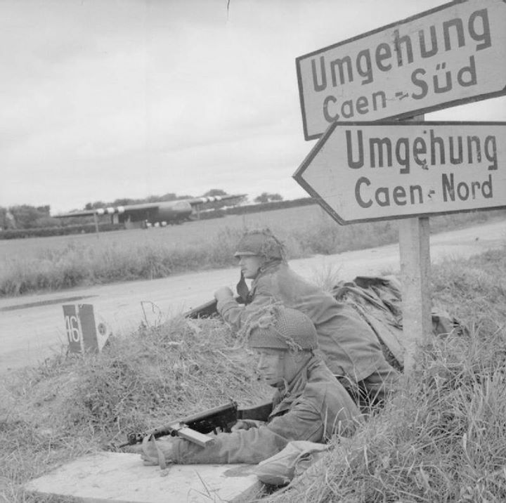 Lance Corporal A. Burton and Lance Corporal L. Barnett of British 6th Airborne Division at a road junction near Ranville France 7 June 1944. Note Horsa glider in background.
