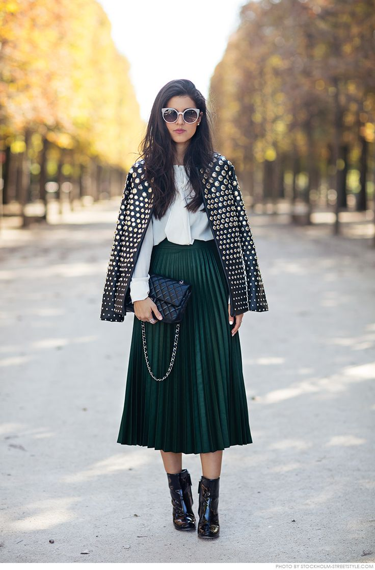 Pamela Allier street style: studded leather jacket, plissed midi skirt dark green, white collared shirt, black ankle boots