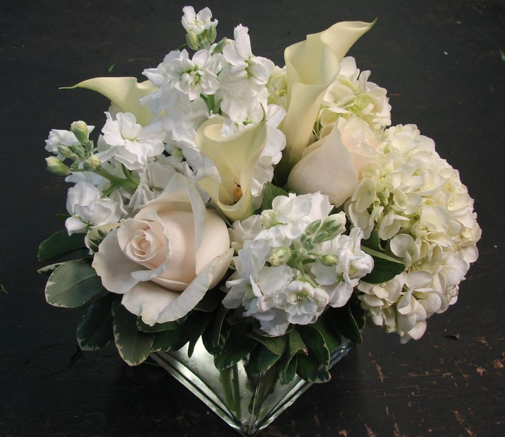 This is a cube vase floral arrangement that features roses, stock and hydrangea in a white and cream color scheme.  See our entire selection at www.starflor.com.  To purchase any of our floral selections, as gifts or décor, please call us at 800.520.8999 or visit our e-commerce portal at www.Starbrightnyc.com. This composition of flowers is generally available for same day delivery in New York City (NYC). SQ094