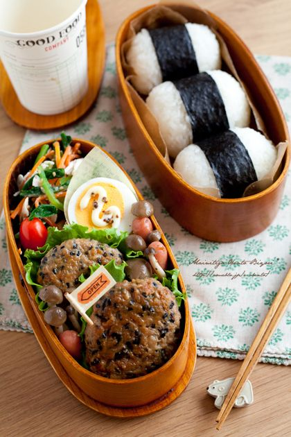 Japanese style hamburger, sauteed mushrooms and sausage, egg, tossed sesame with vegetables, rice balls, and cherry tomato.