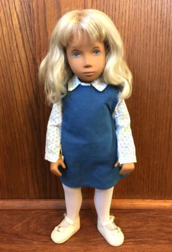 Tunic Sasha will be wearing a white long sleeved blouse with a tiny blue print. Her pinafore/tunic is blue. She wears white tights and white court shoes. The shoes in photo are not the correct shoes for the original outfit