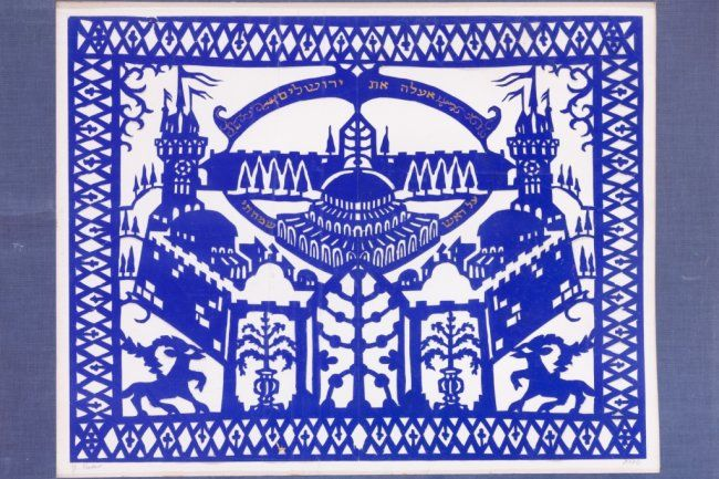 "Mizrach-Shiviti by Yehudit Shadur. Papercut, blue on white background. The theme being the walled city of Jerusalem featuring medival-type towers and centering a depiction of the Temple, and the Hebrew words ""I shall place Jerusaolem above my chiefest joys,"" and at bottom a pair of stags flanking a stylized seven-branched Menorah. Signed in English and in Hebrew. 13.5"" x17"". (34 X 43.5 cm.) $1,500 – 2,000"