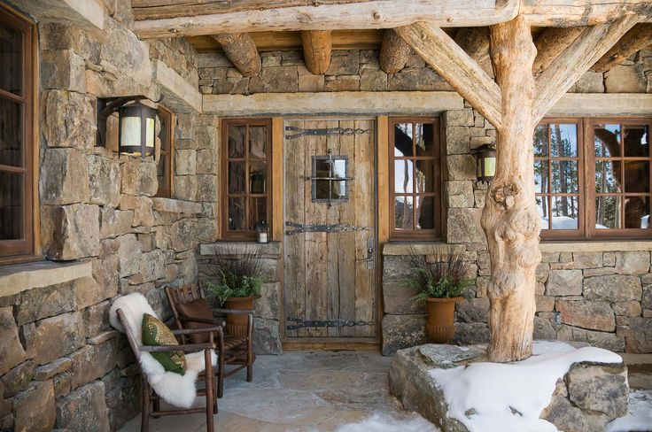 Beautiful cabin entry.  Rock walls, rustic lighting, small wooden windows, natural wood porch posts