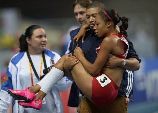 Allyson Felix tore her hamstring during the 200 meter race and was carried away by her older brother Wes.  Beautiful picture.