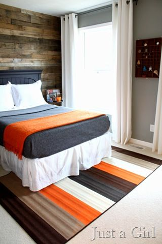 pallet wall and orange/gray color combo for tween boys room- I like the simple design for the laying of the bed clothes and the simple grommet curtains. Easy to reproduce with your own colors.
